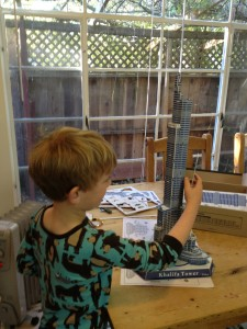 Unschooling in action: building a model of the world's tallest building while still in pajamas.